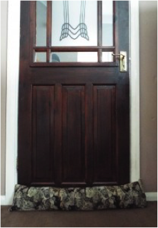 Brown front door with a draft excluder
